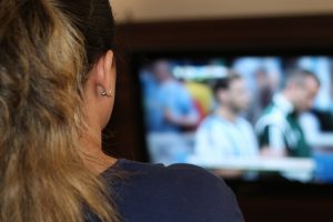 woman watching fifa through IPTV distribution